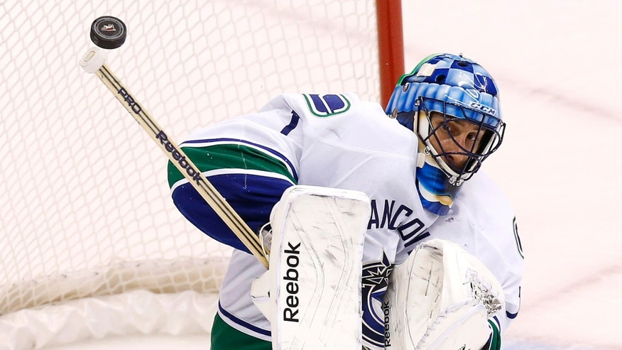 Vancouver Canucks' Roberto Luongo makes a save on a shot by the Phoenix Coyotes during the second period of an NHL hockey game on Tuesday, Nov. 5, 2013, in Glendale, Ariz. (AP Photo/Ross D. Franklin)