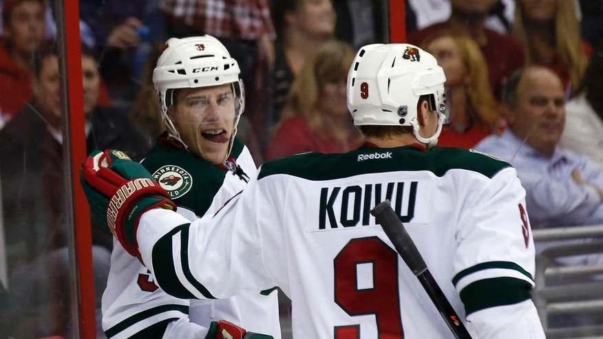 Minnesota Wild center Charlie Coyle, left, celebrates his goal with center Mikko Koivu (9), from Finland, in the first period of an NHL hockey game against the Washington Capitals, Thursday, Nov. 7, 2013, in Washington. (AP Photo/Alex Brandon)