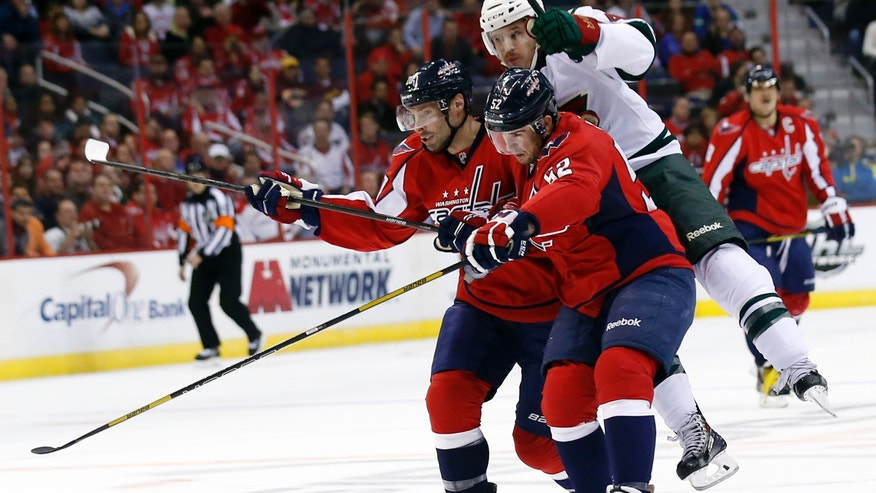 Washington Capitals right wing Troy Brouwer, left, and defenseman Mike Green (52) combine to block Minnesota Wild right wing Justin Fontaine during the first period of an NHL hockey game, Thursday, Nov. 7, 2013, in Washington. (AP Photo/Alex Brandon)