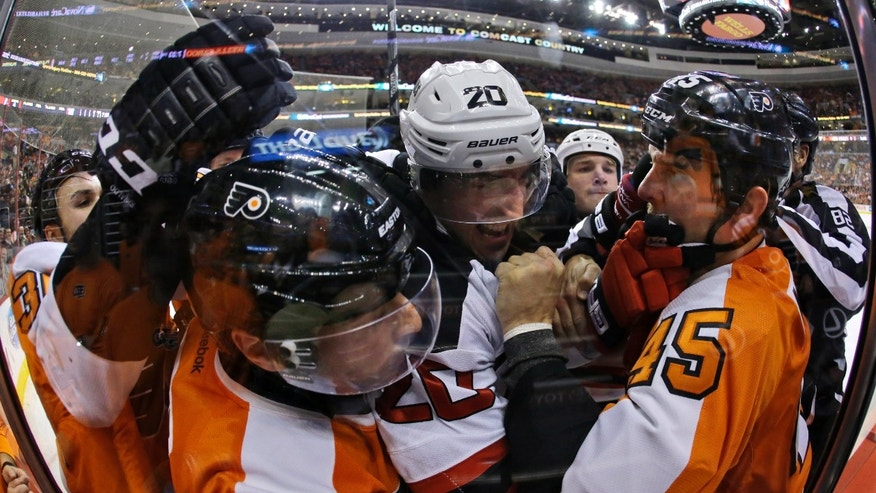 Philadelphia Flyers' Kris Newbury (45), Mark Streit, second from left, of Switzerland, and Zac Rinaldo, left, battle with New Jersey Devils' Ryan Carter (20) during the first period of an NHL hockey game on Thursday, Nov. 7, 2013, in Philadelphia. (AP Photo/Matt Slocum)