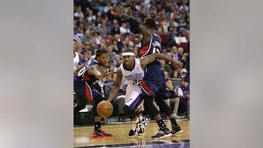Sacramento Kings guard Isaiah Thomas, center, drives between Atlanta Hawks Cartier Martin, left, and Dennis Schroder, of Germany, right, during the third quarter of an NBA basketball game in Sacramento, Calif., Tuesday, Nov. 5, 2013.  The Hawks won 105-100.(AP Photo/Rich Pedroncelli)
