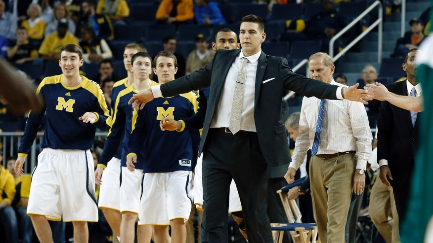 Michigan Mitch McGary greets players during a timeout against Wayne State in the first half of an exhibition NCAA basketball game in Ann Arbor, Mich., Monday, Nov. 4, 2013. (AP Photo/Paul Sancya)