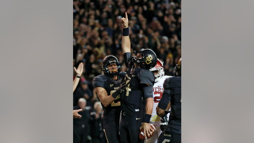 Baylor 's Clay Fuller, left, celebrates with quarterback Bryce Petty, pointing to the sky after Petty kept the ball on a running play for a score against Oklahoma in the first half of an NCAA college football game, Thursday, Nov. 7, 2013, in Waco, Texas. (AP Photo/Tony Gutierrez)