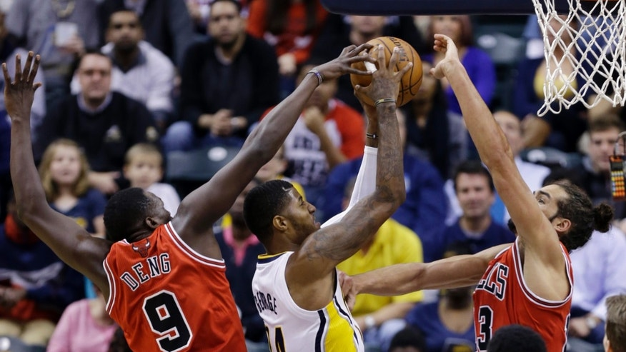 Indiana Pacers forward Paul George, center, is fouled as he shoots between Chicago Bulls forward Luol Deng, left, and center Joakim Noah in the first half of an NBA basketball game in Indianapolis, Wednesday, Nov. 6, 2013.  (AP Photo/Michael Conroy)