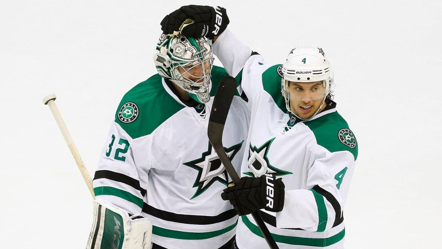 Dallas Stars goalie Kari Lehtonen (32), of Finland, and defenseman Brenden Dillon (4) celebrate their 4-3 win in overtime against the Detroit Red Wings after an NHL hockey game in Detroit Thursday, Nov. 7, 2013. (AP Photo/Paul Sancya)