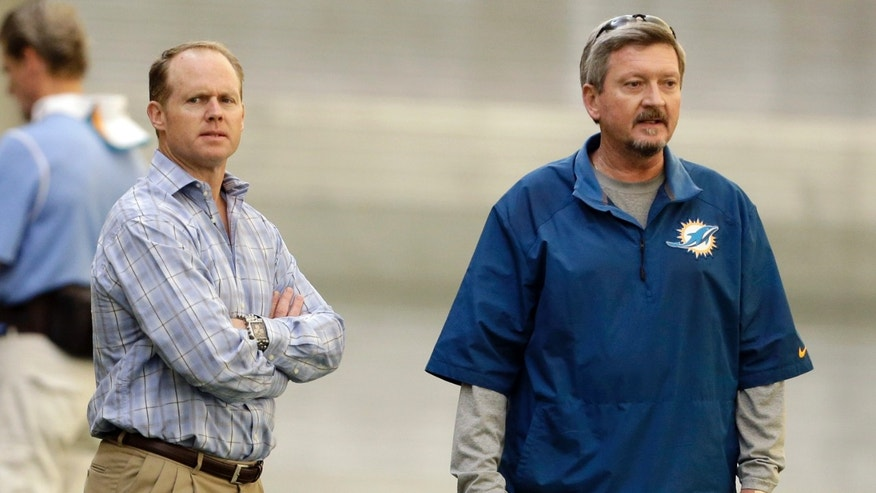 Miami Dolphins general manager Jeff Ireland, left, stands with head trainer Kevin O'Neill, right, during the NFL football team's practice Wednesday, Nov. 6, 2013, in Davie, Fla. (AP Photo/Lynne Sladky)