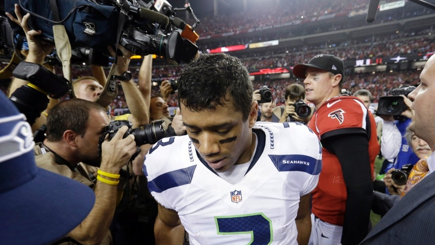 FILE - In this Jan . 13, 2013 file photo, Seahawks quarterback Russell Wilson leaves the field after shaking hands with Atlanta Falcons quarterback Matt Ryan after an NFC divisional playoff NFL football game in Atlanta. The Falcons won 30-28. The NFC divisional playoff game in Atlanta last January was nearly a crowning moment for Wilson and the Seahawks, overcoming a 20-point deficit to take a late lead. It all disappeared in the final 31 seconds and even 10 months later remains a sore spot that gets highlighted this week with the Seahawks headed back to Atlanta. (AP Photo/David Goldman, File)
