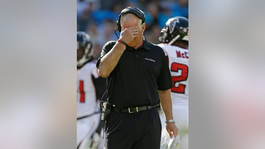 Atlanta Falcons head coach Mike Smith puts his hand over his face as he walks back to the sidelines in the second half of an NFL football game against the Carolina Panthers in Charlotte, N.C., Sunday, Nov. 3, 2013. (AP Photo/Bob Leverone)