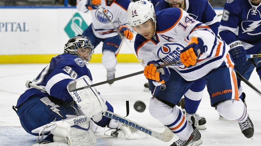 Tampa Bay Lightning goalie Ben Bishop (30) makes a kick-save on a shot by Edmonton Oilers right wing Jordan Eberle (14) during the third period of an NHL hockey game on Thursday, Nov. 7, 2013, in Tampa, Fla. (AP Photo/Chris O'Meara)