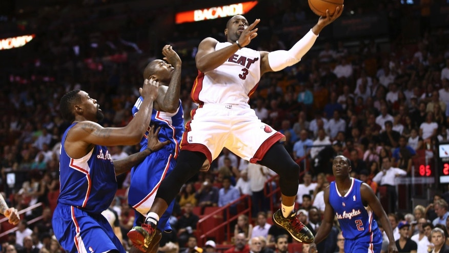 Miami Heat's Dwyane Wade (3) drives between Los Angeles Clippers players DeAndre Jordan, left, Jamal Crawford, second from left, and Darren Collison (2) for two points during the first half of an NBA basketball game in Miami, Thursday, Nov. 7, 2013. (AP Photo/J Pat Carter)