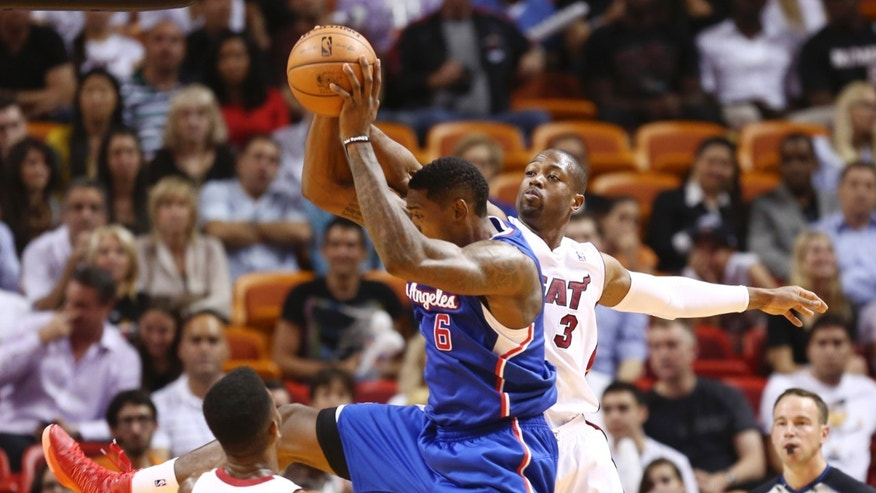 Miami Heat's Norris Cole (30) and Dwyane Wade (3) try to block Los Angeles Clippers' DeAndre Jordan (6) during the first half of an NBA basketball game in Miami, Thursday, Nov. 7, 2013. (AP Photo/J Pat Carter)