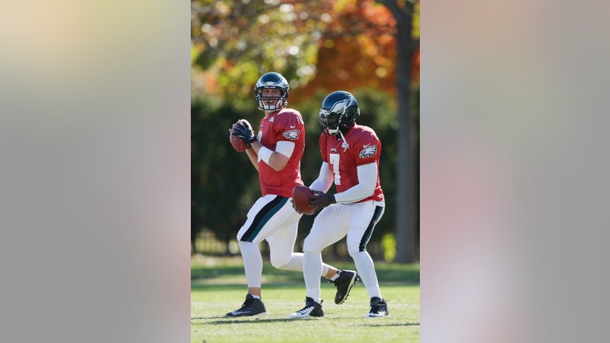 Philadelphia Eagles quarterback Nick Foles (9) and quarterback Michael Vick go back to pass during practice at the NFL football team's training facility, Wednesday, Nov. 6, 2013, in Philadelphia. (AP Photo/Matt Rourke)