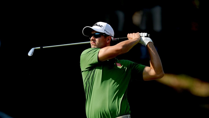 In this photo released by OneAsia, Adam Scott of Australia plays a shot during the second round of the Australian PGA Championship at the RACV Royal Pines Resort golf club on Australia's Gold Coast Friday, Nov. 8, 2013. (AP Photo/OneAsia, Khalid Redza) NO LICENSING