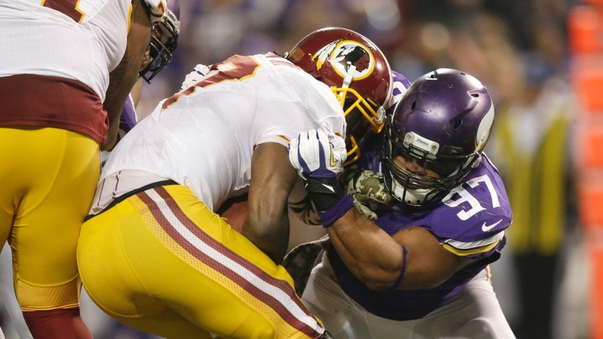 Washington Redskins quarterback Robert Griffin III, left, is sacked by Minnesota Vikings defensive end Everson Griffen during the second half of an NFL football game Thursday, Nov. 7, 2013, in Minneapolis. The Vikings won 34-27. (AP Photo/Jim Mone)