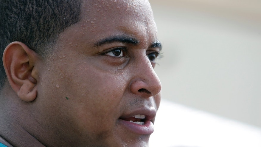 FILE - In this July 22, 2013, file photo, Miami Dolphins tackle Jonathan Martin in interviewed after an NFL football practice in Davie, Fla. In the stadium program sold at the Miami Dolphins' game on Halloween, Richie Incognito was asked who's the easiest teammate to scare. His answer: Jonathan Martin.  The troubled, troubling relationship between the two offensive linemen took an ominous turn Monday, Nov. 4, 2013, with fresh revelations: Incognito sent text messages to his teammate that were racist and threatening, two people familiar with the situation said.(AP Photo/Lynne Sladky, File)
