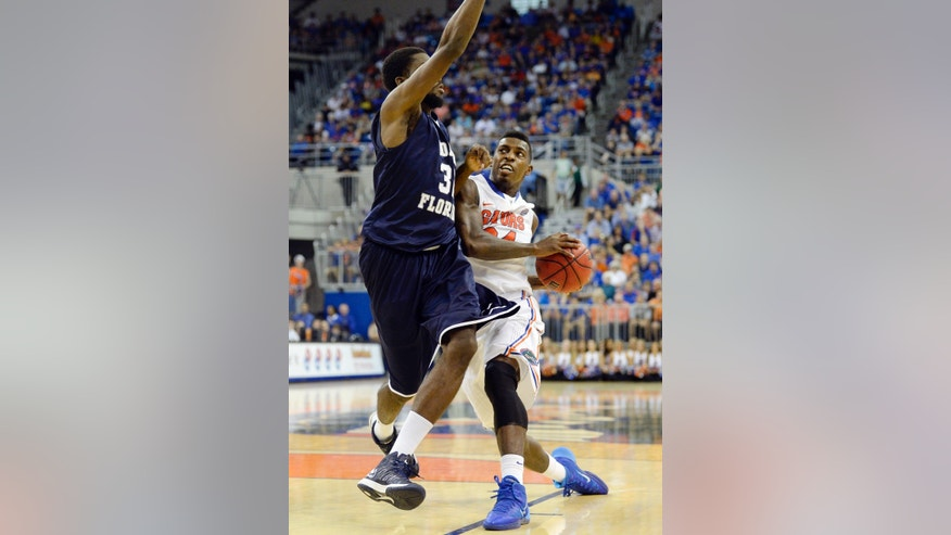 Florida forward Casey Prather (24) rushes for the basket as North Florida forward Demarcus Daniels (32) defends during the first half of an NCAA college basketball game, Friday, Nov. 8, 2013, in Gainesville, Fla.  (AP Photo/Phil Sandlin)