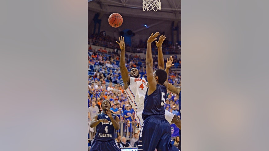 Florida center Patric Young (4) shoots North Florida forward Charles McRoy (5) during the first half of an NCAA college basketball game, Friday, Nov. 8, 2013, in Gainesville, Fla. (AP Photo/Phil Sandlin