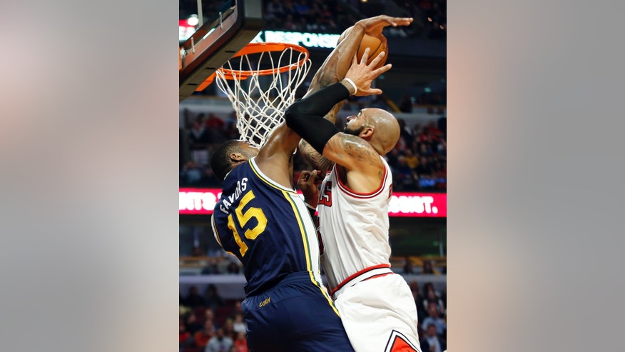 Chicago Bulls forward Carlos Boozer, right, goes to the basket against Utah Jazz forward Derrick Favors (15) during the first quarter of an NBA basketball game in Chicago, Friday, Nov. 8, 2013. (AP Photo/Kamil Krzaczynski)