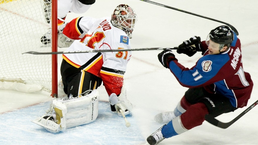 Calgary Flames goalie Karri Ramo (31), of Finland, watches as Colorado Avalanches' Jamie McGinn (11) misses the puck in front of the net during the first period of an NHL hockey game on Friday, Nov. 8, 2013, in Denver. (AP Photo/Barry Gutierrez)