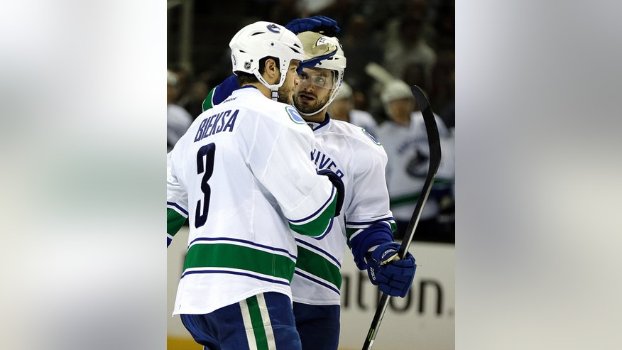 Vancouver Canucks' Kevin Bieksa, left, and Brad Richardson celebrate after Bieksa scored against the San Jose Sharks during the second period of an NHL hockey game on Thursday, Nov. 7, 2013, in San Jose, Calif. (AP Photo/Ben Margot)