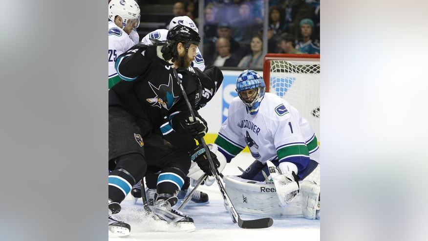 Vancouver Canucks goalie Roberto Luongo, right, defends against San Jose Sharks' Joe Thornton during the first period of an NHL hockey game on Thursday, Nov. 7, 2013, in San Jose, Calif. (AP Photo/Ben Margot)
