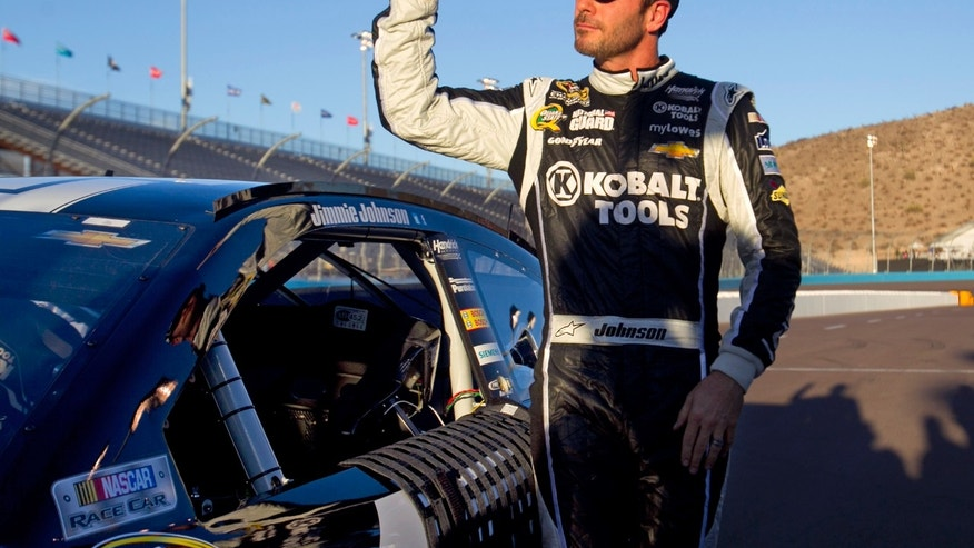 Jimmie Johnson gives a thumbs-up after winning the pole for the NASCAR Sprint Cup Series auto race, Friday afternoon, Nov. 8, 2013, at Phoenix International Raceway in Avondale, Ariz. (AP Photo/The Arizona Republic. David Wallace) MARICOPA COUNTY OUT  NO SALES