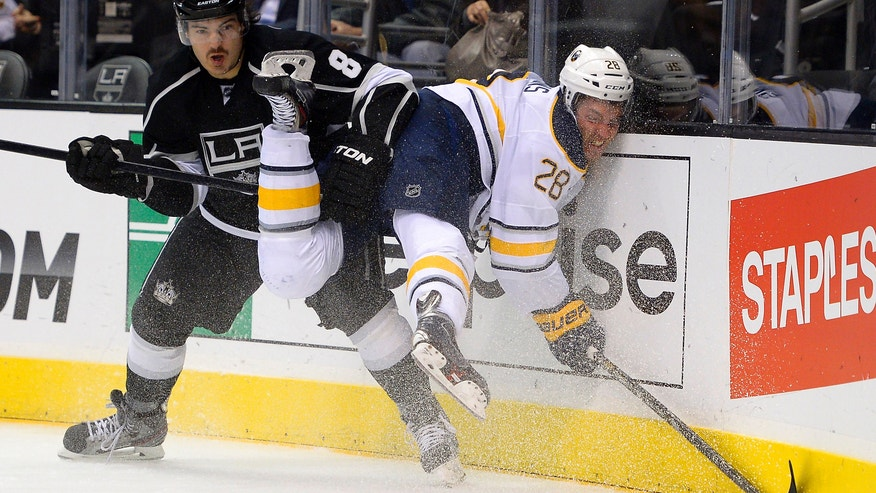 Buffalo Sabres center Zemgus Girgensons, right, of Latvia, slams into the boards as he competes for the puck with Los Angeles Kings defenseman Drew Doughty during the first period of an NHL hockey game, Thursday, Nov. 7, 2013, in Los Angeles. (AP Photo/Mark J. Terrill)