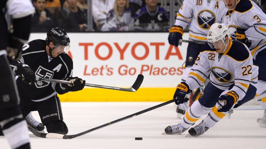 Los Angeles Kings center Mike Richards, left, and Buffalo Sabres left wing Johan Larsson, of Sweden, compete for the puck during the first period of an NHL hockey game, Thursday, Nov. 7, 2013, in Los Angeles. (AP Photo/Mark J. Terrill)