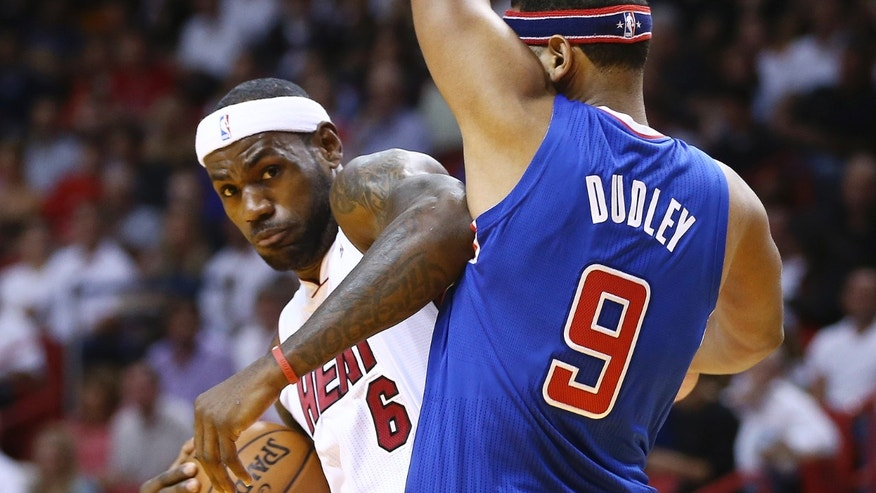 Miami Heat's LeBron James (6) tries to get around Los Angeles Clippers' Jared Dudley (9) during the first half of an NBA basketball game in Miami, Thursday, Nov. 7, 2013. (AP Photo/J Pat Carter)