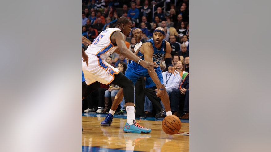Dallas Mavericks shooting guard Vince Carter (25) passes around Oklahoma City Thunder small forward Kevin Durant (35) during the first half of an NBA basketball game in Oklahoma City, Wednesday Nov. 6, 2013. (AP Photo/Brett Deering)