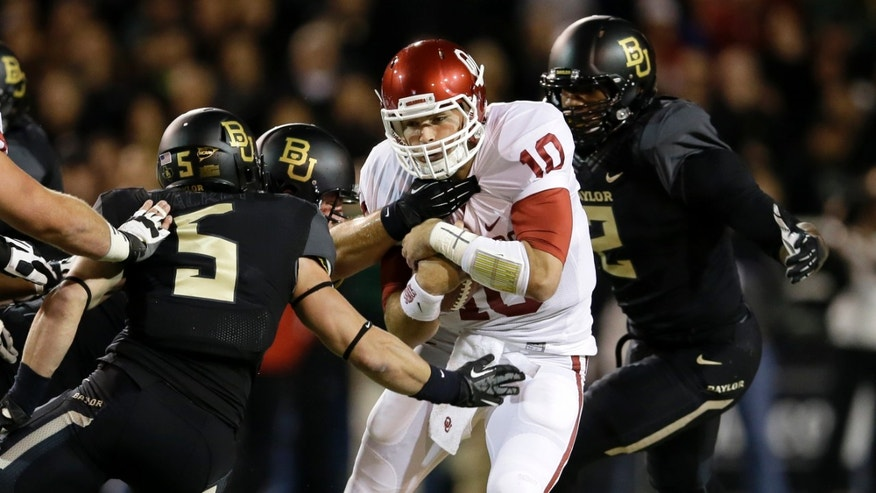 Oklahoma quarterback Blake Bell (10) is caught scrambling out of the pocket by Baylor 's Eddie Lackey (5) and Shawn Oakman (2) in the first half of an NCAA college football game, Thursday, Nov. 7, 2013, in Waco, Texas. (AP Photo/Tony Gutierrez)