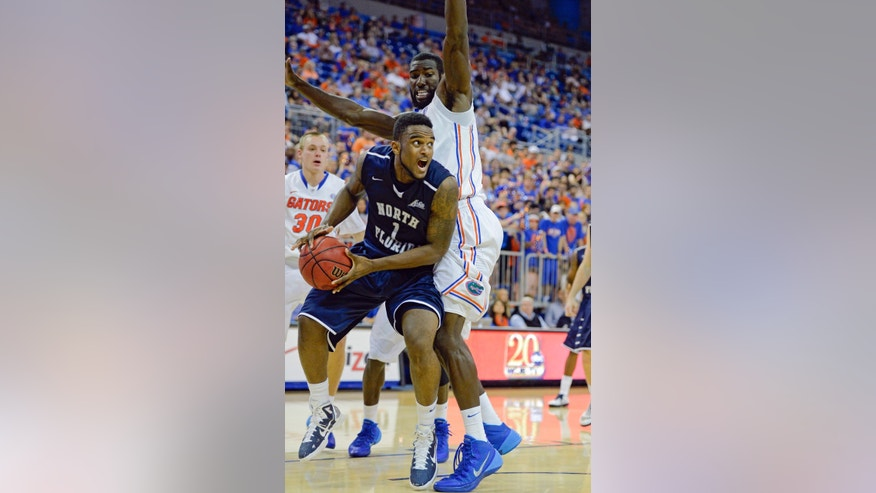 North Florida forward Travis Wallace (1) tries to get to the basket as Florida's Patric Young defends during the second half of an NCAA college Basketball game Friday, Nov. 8, 2013, in Gainesville, Fla. Florida won 77-69. (AP Photo/Phil Sandlin