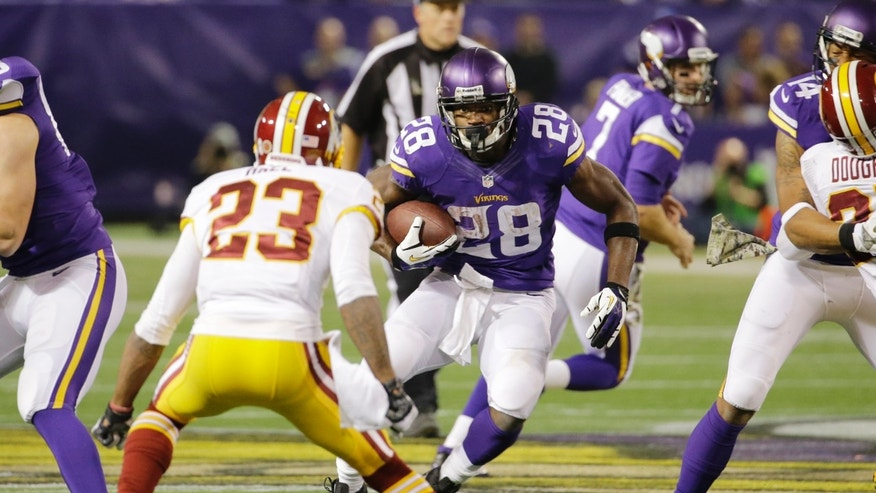 Minnesota Vikings running back Adrian Peterson (28) looks to get past Washington Redskins cornerback DeAngelo Hall (23) during the second half of an NFL football game, Thursday, Nov. 7, 2013, in Minneapolis. (AP Photo/Ann Heisenfelt)