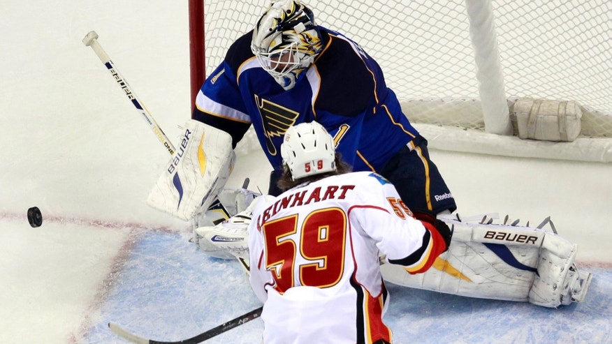 St. Louis Blues goalie Brian Elliott, top, deflects the puck as Calgary Flames' Max Reinhart watches during the second period of an NHL hockey game Thursday, Nov. 7, 2013, in St. Louis. (AP Photo/Jeff Roberson)