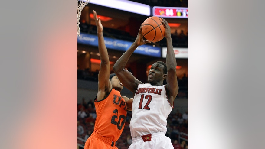 Louisville's Mangok Mathiang, right, pulls down a rebound against Pikeville's John Nunnally during the second half of an NCAA college basketball exhibition game, Wednesday, Nov. 6, 2013, in Louisville, Ky. Louisville defeated Pikeville 90-61. (AP Photo/Timothy D. Easley)