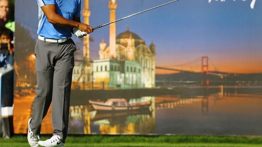 Tiger Woods of the United States watches the flight of his tee shot from the18th tee during the first round of the Turkish  Open golf tournament at the Montgomerie Maxx Royal Course in Antalya, Turkey, Friday, Nov. 8, 2013. An image of Istanbul's Ortakoy Mosque and Bosporus Bridge are in the background.(AP Photo/Kaan Soyturk)