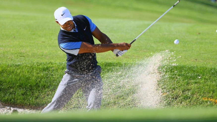 Tiger Woods of the U.S plays a shot from a bunker near the 13th green during the the first round of the Turkish Airlines Open golf tournament at the Montgomerie Maxx Royal Course in Antalya, Turkey, Friday, Nov. 8, 2013. (AP Photo/Kaan Soyturk)