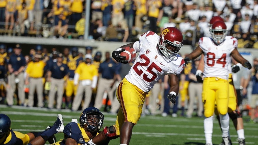 Southern California running back Silas Redd (25) runs past a California defender and scores a touchdown on a pass reception during the first quarter of an NCAA college football game Saturday, Nov. 9, 2013, in Berkeley, Calif. At right is USC wide receiver Darreus Rogers. (AP Photo/Eric Risberg)