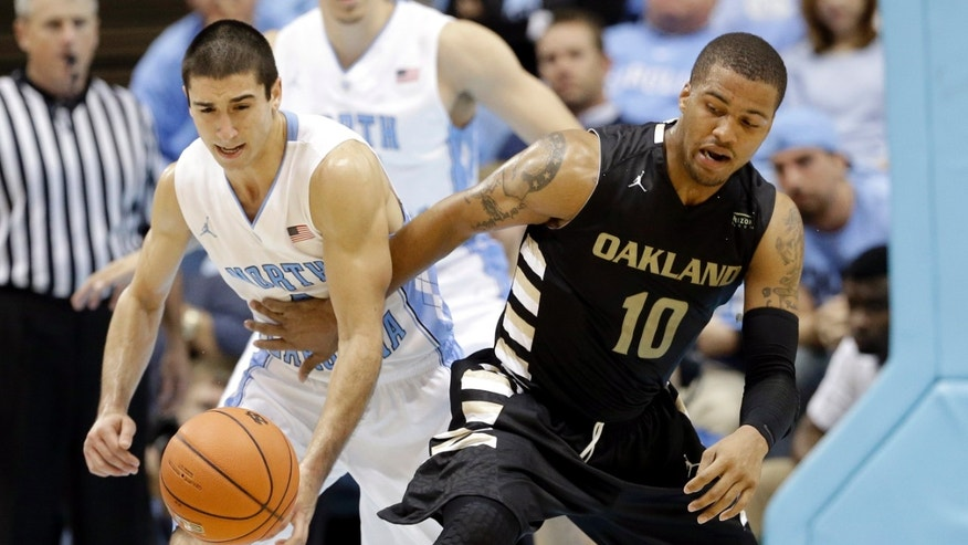 North Carolina's Luke Davis, left, and Oakland's Duke Mondy (10) reach for a loose ball during the second half of an NCAA college basketball game in Chapel Hill, N.C., Friday, Nov. 8, 2013. North Carolina won 84-61. (AP Photo/Gerry Broome)