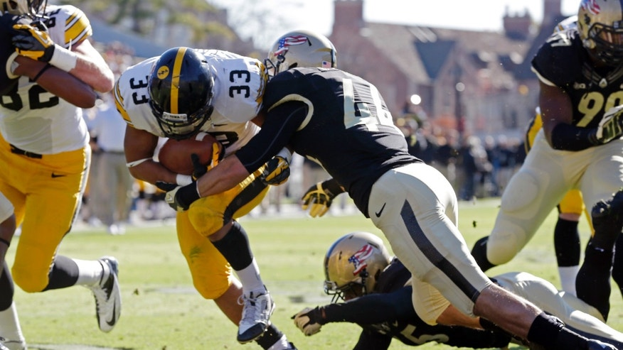 Iowa running back Jordan Canzeri (33) scores a touchdown as he's hit by Purdue safety Landon Feichter during the first half of an NCAA college football game in West Lafayette, Ind., Saturday, Nov. 9, 2013. (AP Photo/Michael Conroy)