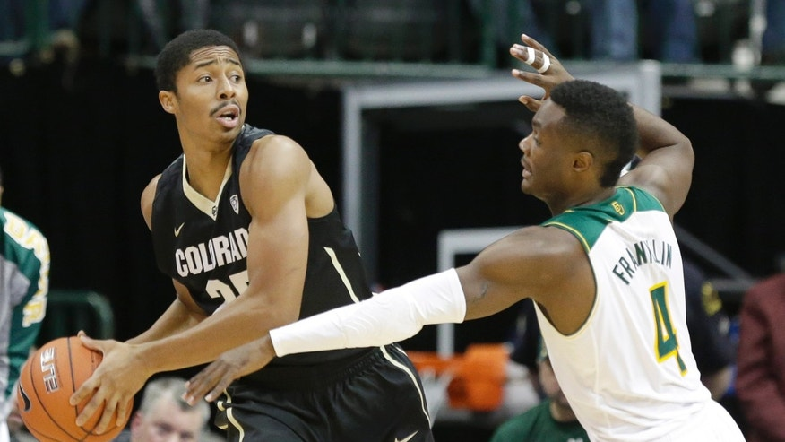 Colorado guard Spencer Dinwiddie (25) looks to pass as Baylor guard Gary Franklin (4) reaches in during the first half of an NCAA college basketball game in Dallas, Friday, Nov. 8, 2013.  (AP Photo/LM Otero)
