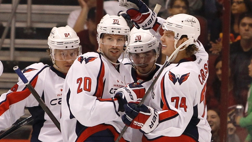 Washington Capitals' John Carlson (74) celebrates with teammates Mikhail Grabovski (84), of Germany; Troy Brouwer (20); and Marcus Johansson (90), of Sweden, after his goal against the Phoenix Coyotes during the second period of an NHL hockey game, Saturday, Nov. 9, 2013 in Glendale, Ariz. (AP Photo/Ralph Freso)