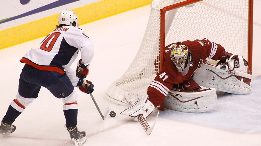 Phoenix Coyotes goaltender Mike Smith (41) makes a stick-save on a shot by Washington Capitals' Marcus Johansson (90), of Sweden, during the first period of an NHL hockey game, Saturday, Nov. 9, 2013, in Glendale, Ariz. (AP Photo/Ralph Freso)