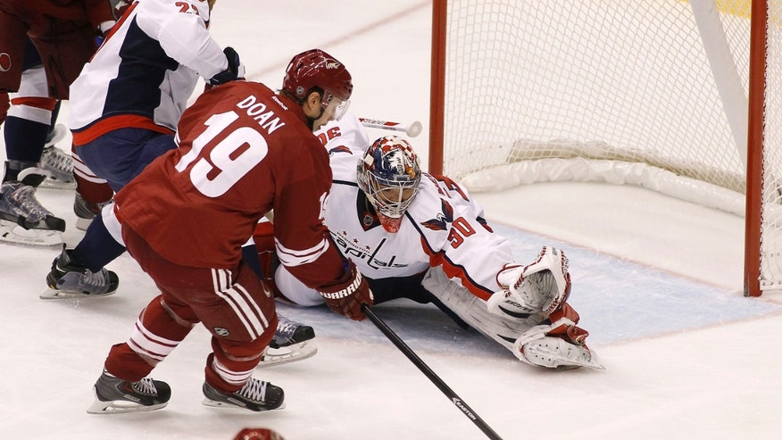 Washington Capitals goaltender Michal Neuvirth, of the Czech Republic, defends as Phoenix Coyotes' Shane Doan moves in for a shot during a power play, as Capitals' Karl Alzner (27) also defends during the first period of an NHL hockey game, Saturday, Nov. 9, 2013 in Glendale, Ariz. (AP Photo/Ralph Freso)