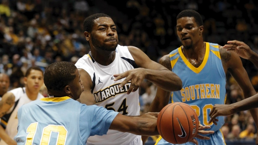 Marquette's Davante Gardner is fouled as he drives between Southern University's Cameron Monroe (10) and Calvin Godfrey during the first half of an NCAA college basketball game Friday, Nov. 8, 2013, in Milwaukee. (AP Photo/Morry Gash)