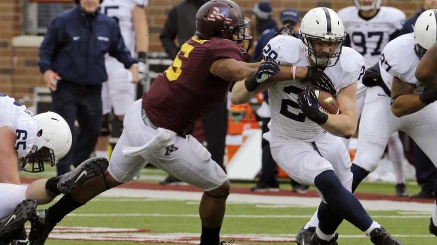 Penn State running back Zach Zwinak (28) tries to break the tackle of Minnesota defensive lineman Theiren Cockran (55) as he carries the ball for an 11-yard gain in the second quarter of an NCAA college football game in Minneapolis, Saturday, Nov. 9, 2013. (AP Photo/Ann Heisenfelt)