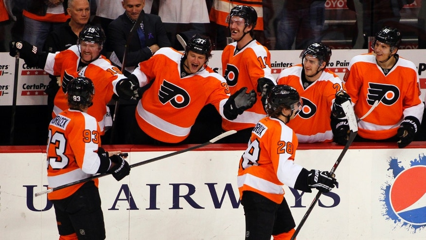 Philadelphia Flyers' captain Claude Giroux, right, who scored his first goal of the season, is followed by Jakub Voracek, who got the assist,  as they skate past their teammates on the bench during the third period of an NHL hockey game with the Edmonton Oilers, Saturday, Nov. 9, 2013, in Philadelphia. The Flyers won 4-2. (AP Photo/Tom Mihalek)