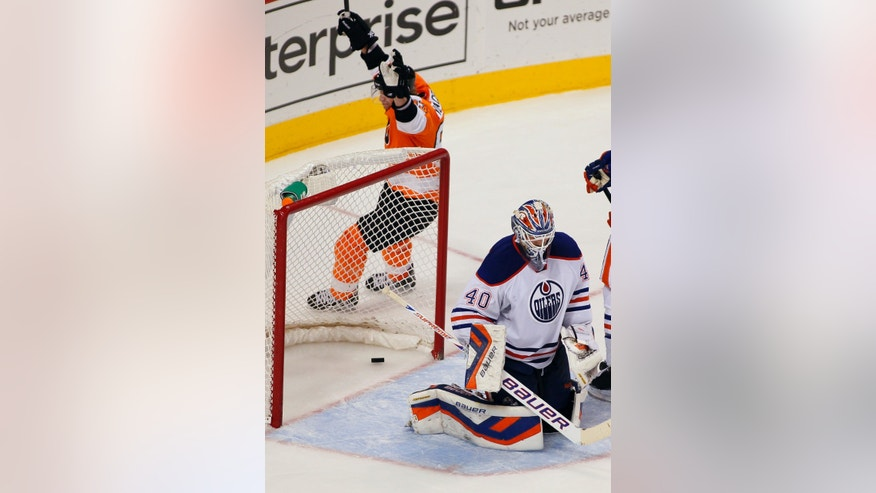 Philadelphia Flyers' Jakub Voracek raises his arms circling the net where a goal by Claude Giroux lays behind Edmonton Oilers goalie Devan Dubnyk during the third period of an NHL hockey game, Saturday, Nov. 9, 2013, in Philadelphia. The Flyers won 4-2. (AP Photo/Tom Mihalek)