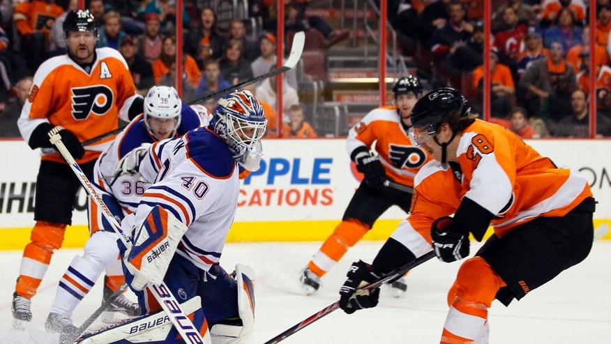 Edmonton Oilers goalie Devan Dubnyk defends as Philadelphia Flyers' Claude Giroux attempts to score during the second period of an NHL hockey game, Saturday, Nov. 9, 2013, in Philadelphia. Looking on at rear are Flyers' Scott Hartnell and Oilers' Philip Larsen. (AP Photo/Tom Mihalek)