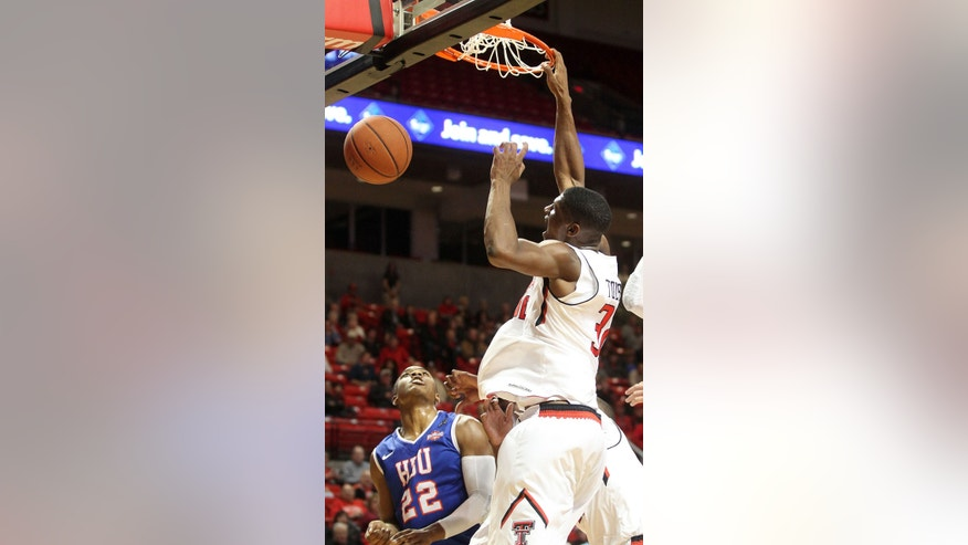 Texas Tech's Jordan Tolbert dunks over Houston Baptist's Dauson Womack during an NCAA college basketball game in Lubbock, Texas, Friday, Nov. 8, 2013. (AP Photo/Lubbock Avalanche-Journal,Tori Eichberger)